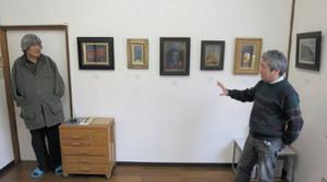 展示された絵の傍らで話す水村さん(左)と田渡さん=大垣市藤江町の画廊春で