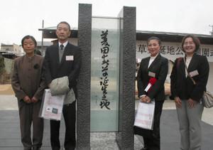 横山大観の書によるモニュメントと記念撮影する笹本さん(右から2人目)=飯田市仲ノ町で