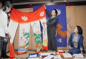 氷見から持参した花嫁のれんを広げる谷内和子会長(中)=石川県七尾市の一本杉通りで