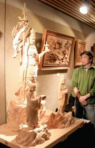 制作した毘沙門天三尊像を紹介する藤崎秀平さん=南砺市北川で