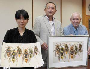 原画(右)とレプリカ(左)を手にする(右から)田淵さん、斎藤さん、中嶋さん=安曇野市の牧区公民館で