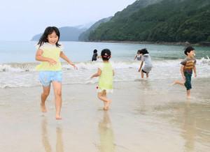 雨の中、波打ち際ではしゃぐ子どもたち=尾鷲市三木里町の三木里ビーチで