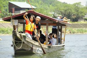 船頭の指導を受けながら、櫂を使って操船する児童ら=関市小瀬の長良川で