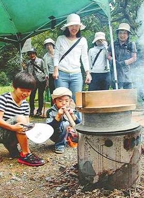 炊飯体験で竹筒を使って火の勢いを調整する子どもたち=敦賀市の中池見湿地で