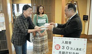 秋山稔館長(右)から記念品を受け取る30万人目の入館者細川祥代さん(左)=金沢市下新町で
