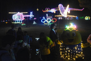 色鮮やかなイルミネーションを背景に電飾を身にまとうまっくんとカメラを向ける人たち=南箕輪村の信州大芝高原で