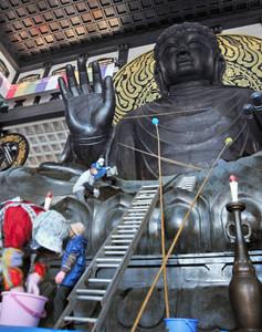 越前大仏のすすやほこりを払うボランティアたち=勝山市の大師山清大寺で