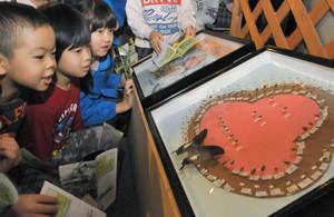 昆虫の標本で描かれたサルのパネルに見入る子どもたち=県ふれあい昆虫館で