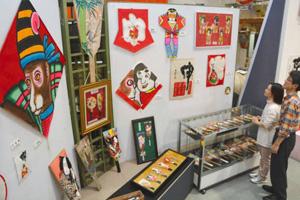 華やかなデザインのたこと羽子板が並ぶ会場=東近江市の東近江大凧会館で