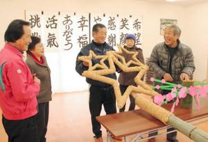 星形のシンボルを竹柱に取り付ける会員たち=小矢部市の桜町JOMONパークで