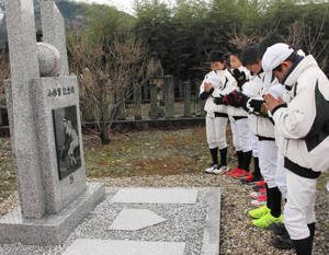 完成した小林繁さんの記念碑に手を合わせるオールスター福井の選手たち=永平寺町東古市の本覚寺で