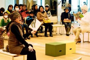 親子連れらに絵本を朗読する朗読ユニット「おはなしDecoBee♪」のメンバー=富山市図書館で