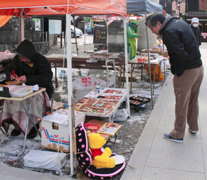 寒空の下、朝市の品定めをする参拝客(右)=多賀町の多賀大社で