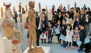彫刻家(中央)の解説を聞き作品を鑑賞する親子連れら=名古屋・栄の県美術館ギャラリーで