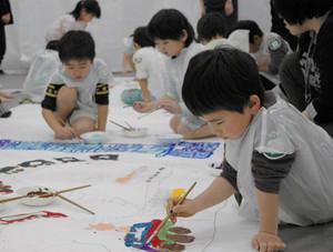 絵筆を操り、作品を仕上げる子どもたち=小矢部市鷲島で