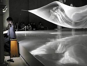 大巻さんの作品を前に演奏する今村さん=岐阜市宇佐の県美術館で