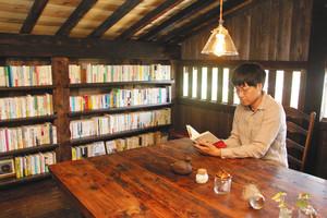 書店に改築した屋根裏で本を読む朝倉さん=高山市国府町宇津江で