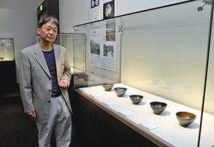 天目茶碗ばかりが並ぶ会場と長江さん=瀬戸市美術館で
