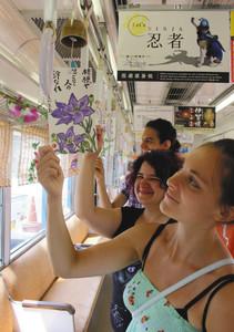 俳句の短冊が付いた風鈴を見つめるイタリアの大学生=伊賀市上野丸之内で