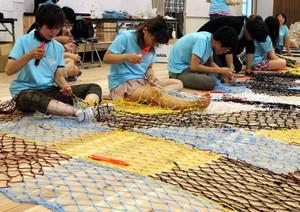 カラフルな糸で漁網を編む現代文化コースの学生たち=豊橋市の愛知大で