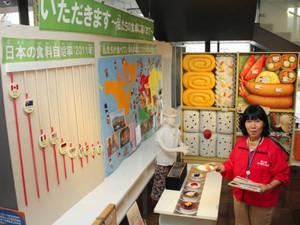 弁当の模型の前で食材の輸入先を説明する加藤有紀さん=名古屋市中村区平池町4で