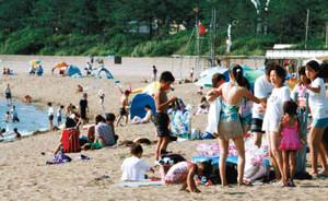 晴れ空の下、海水浴客でにぎわう砂浜=坂井市の三国サンセットビーチで