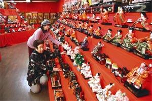 ひな人形の展示作業を進める会員ら=浜松市北区引佐町で