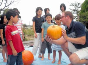 外国人講師に教わりながらカボチャの飾りを作る子どもたち=日進市藤塚で