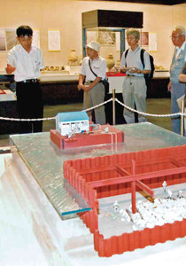 大道和人さん(左端)から展示物の解説を受ける参加者たち=安土町の県立安土城考古博物館で