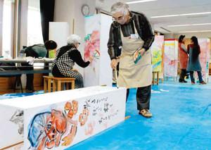 あんどんに思い思いの模様を描きつける参加者たち=松本市美術館で