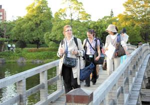 英語の説明を聞き、橋を渡りながら園内の景色を眺める会議参加者=名古屋市熱田区の白鳥庭園で