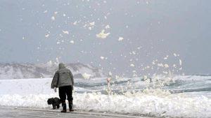 雪景色の中に舞う波の花=輪島市町野町曽々木で