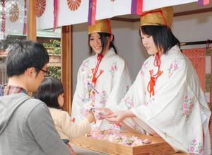 訪れた子どもと造花の小枝を交換する福娘たち(右)=敦賀市の金崎宮で