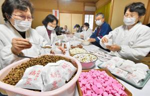 次々と福豆を袋に詰めていく氏子たち=福井市の木田神社で