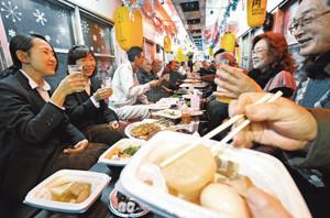 飾り付けられた電車の中で、おでんなどを食べながら宴会を楽しむ利用者たち=越前市内で