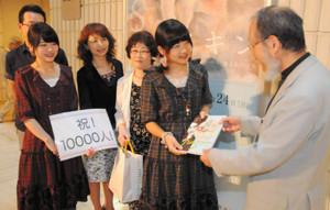 1万人目の来場者となり、古川秀昭館長から記念品を受け取る林由佳子さん(右から2人目)=岐阜市宇佐の県美術館で