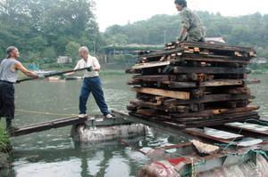 恵那納涼水上花火大会に向け、かがり火で湖面を照らす台船の準備をする人たち=恵那市大井町の恵那峡で