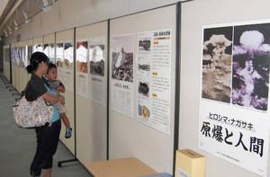 原爆のポスター展を見る母と子=金沢市立泉野図書館で