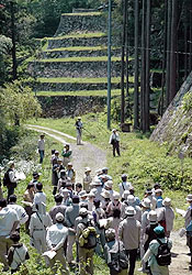 江戸期に築かれたとされる6段の石垣(後方)などを巡る参加者=いずれも恵那市岩村町で