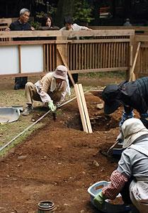 手作業で地中を掘り進め、信長居館跡の手がかりを探す作業員。柵の外から見学できる=岐阜市の岐阜公園で