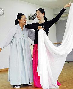 独白劇を演じる在日3世の蔡さん(左)と舞いで参加する黄さん=名古屋市千種区のコリアンスクールで
