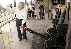 観光客に「腕木式信号機」を説明する今井部長(左)=恵那市の明知鉄道岩村駅で