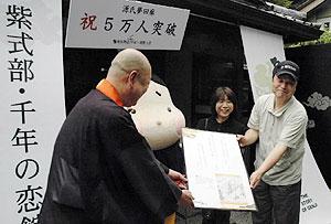 記念のパネルを受ける新野さん夫妻=大津市の石山寺で