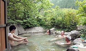 緑に囲まれた露天風呂を楽しむ観光客ら=高山市奥飛騨温泉郷福地温泉で