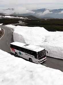 山頂近くの雪壁の間をバスが通行する県道乗鞍岳線=松本市安曇の乗鞍高原で
