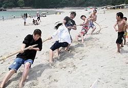 砂浜での綱引きで、熱戦を繰り広げる人たち=尾鷲市三木里町で