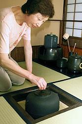 自宅の茶室で茶釜を見せてくれる畠とき子さん=富山県高岡市で