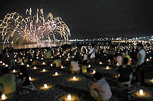 キャンドルの砂浜に上がる水中花火が漁火想のフィナーレを盛り上げる=昨年7月、高浜町事代の城山海水浴場で
