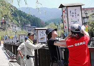 あんどんを谷沿いに飾り付ける人たち=下呂市の下呂温泉街で