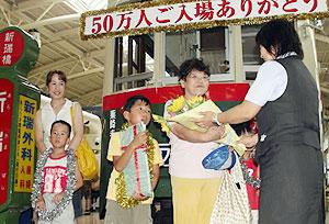 50万人目の入館者に職員から花束を贈られたセレモニー=日進市浅田町のレトロでんしゃ館で